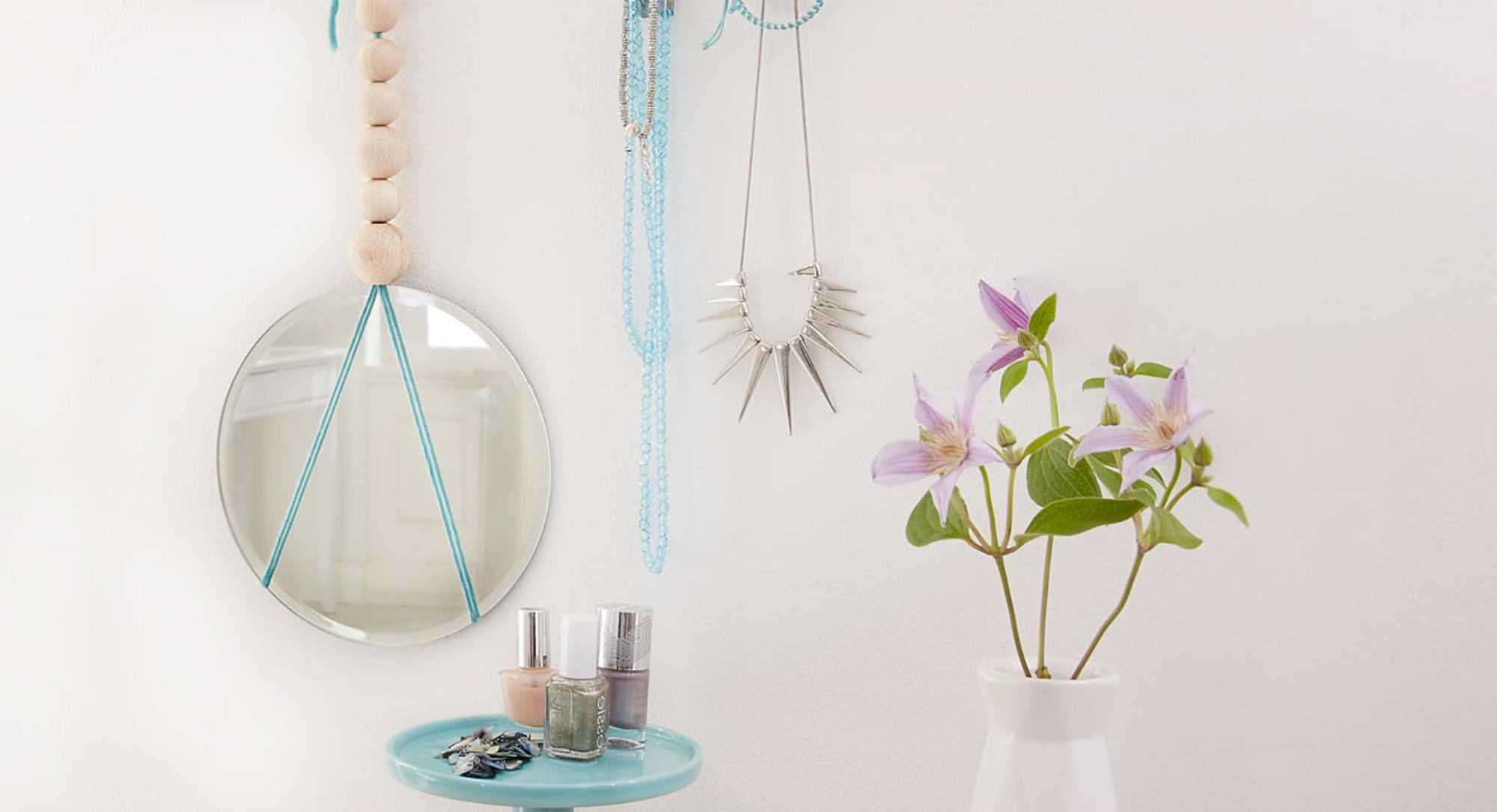 DIY Spiegel mit Holzkugeln hängt an der Wand