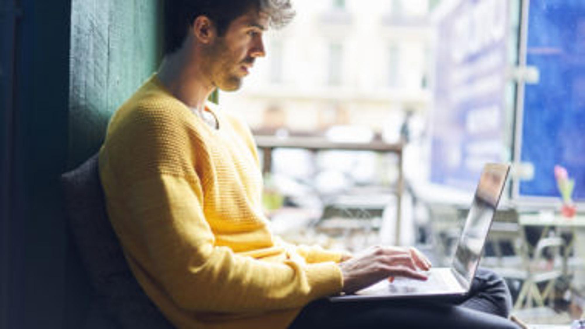 Mann im gelben Pullover tippt auf seinem Laptop