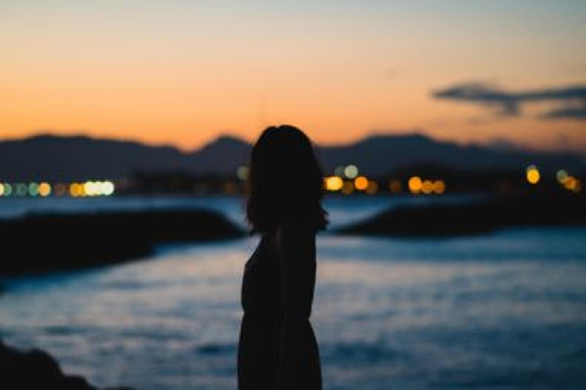 Eine Frau steht in der Dämmerung am Strand.