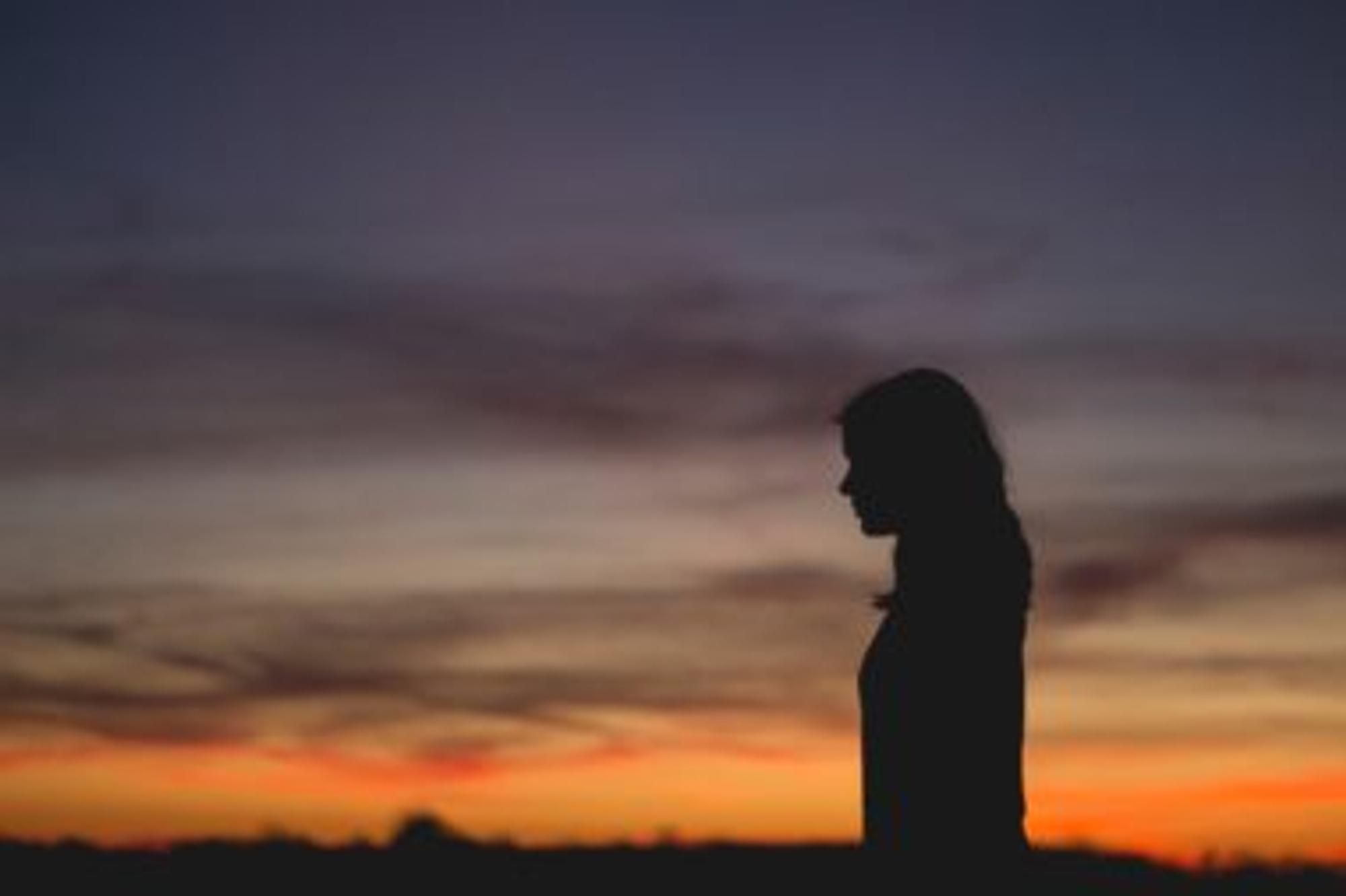 Frau vor Sonnenuntergang - Die Angst vor dem Tod begleitet manche Menschen durch's Leben
