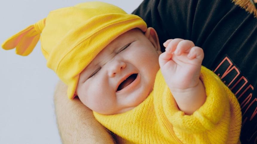 Mann hat Baby im Arm und lässt es quengeln