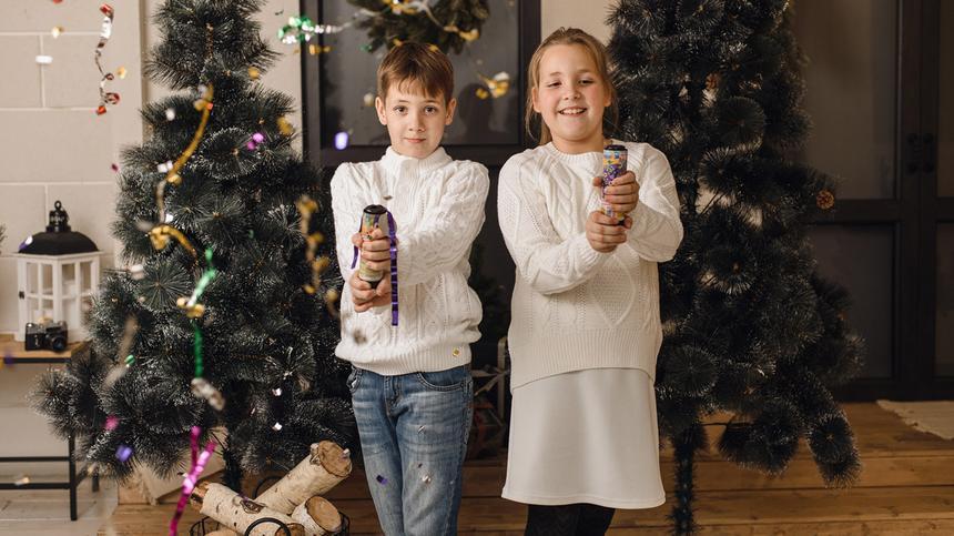 Zwei Kinder lassen je ein Knallbonbon an Silvester hochgehen