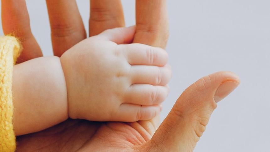 Babyhand umschließt Zeigefinger von Erwachsenem