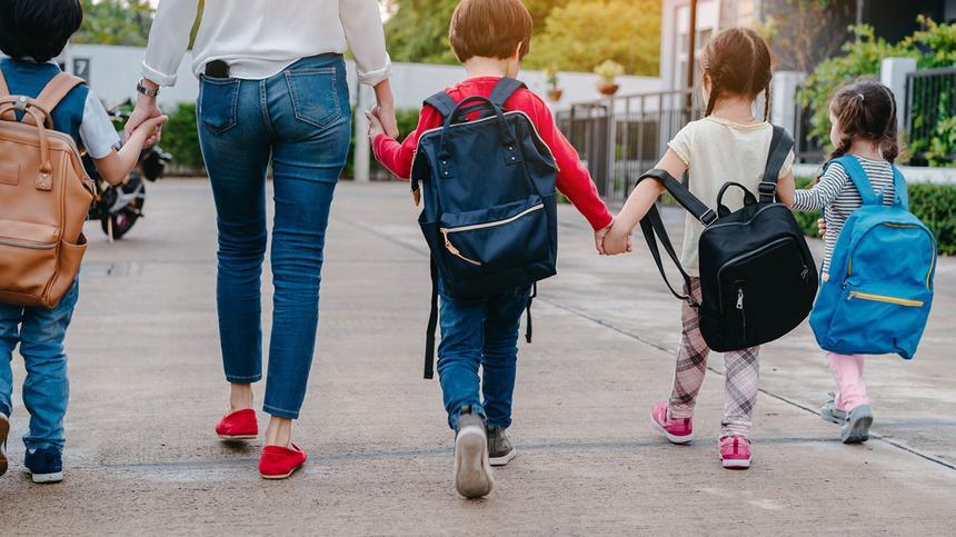Mutter bringt vier Kinder zum Kindergarten