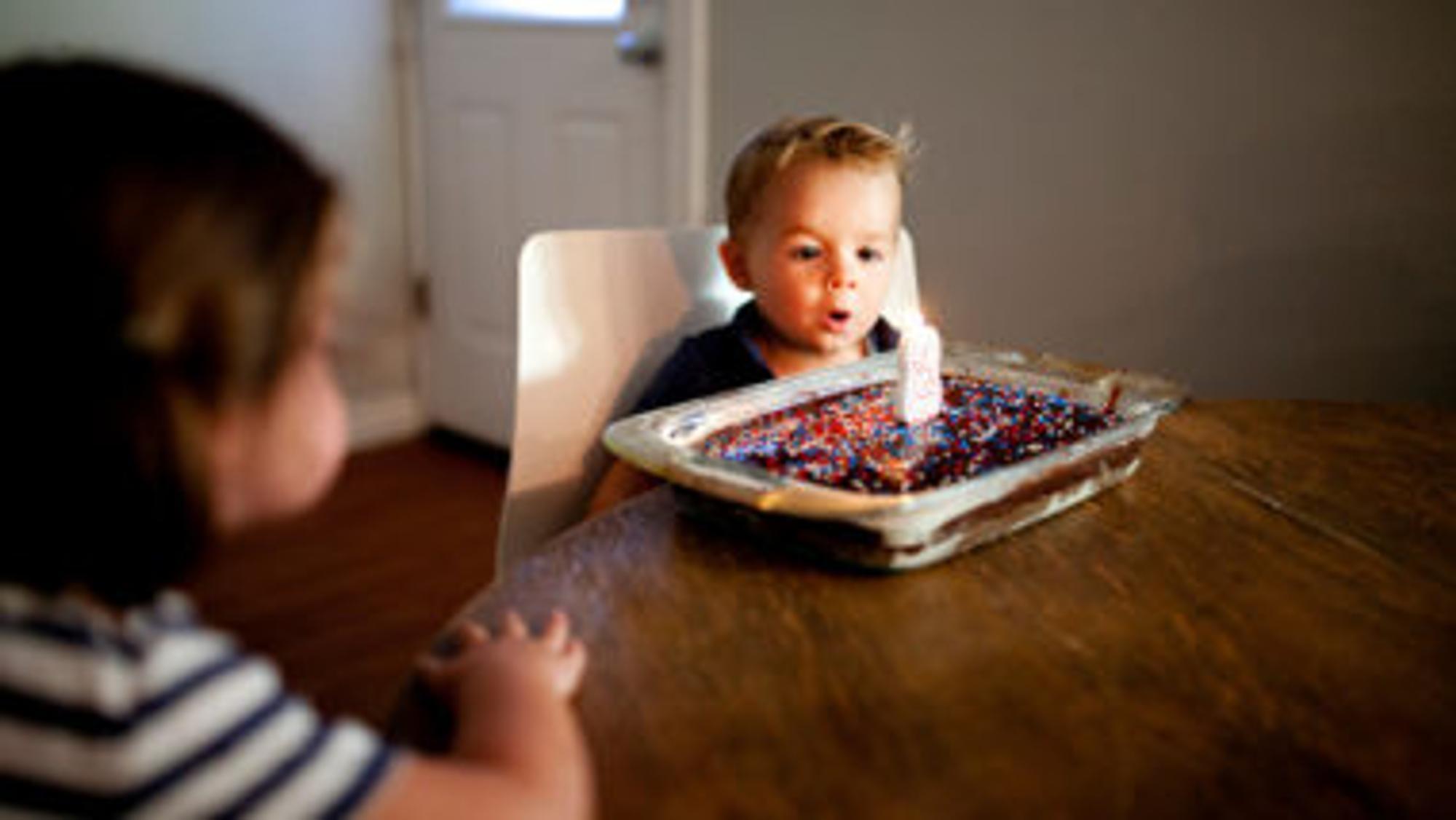 Junge bläst die Kerze auf seinem Geburtstagskuchen aus