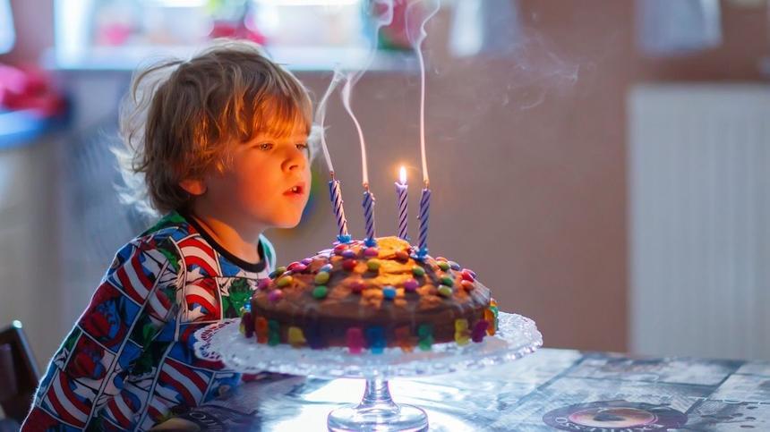 Kind pustet Kerzen auf Kuchen aus