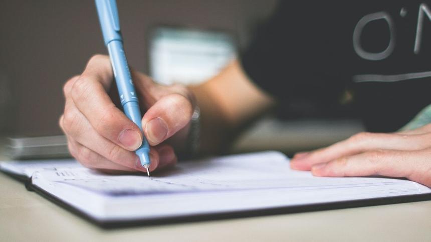 Person schreibt mit Stift etwas in Notizbuch
