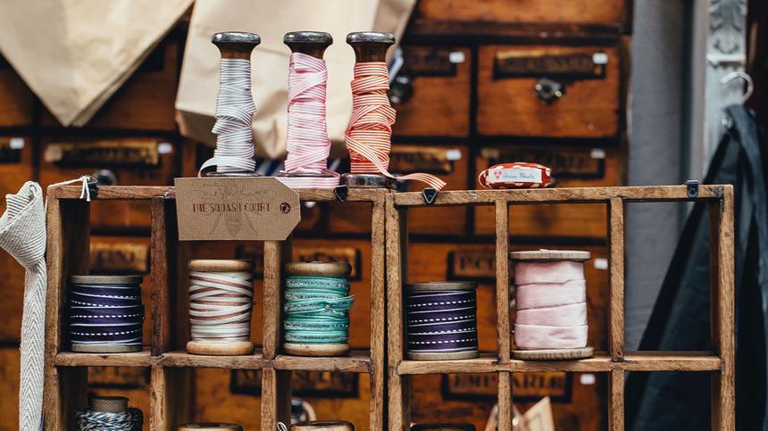 Garnrollen stehen auf einem Holzregal