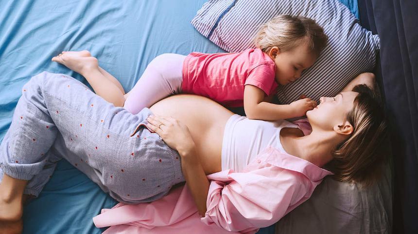 Zweite Schwangerschaft: Schwangere und Kind im Bett