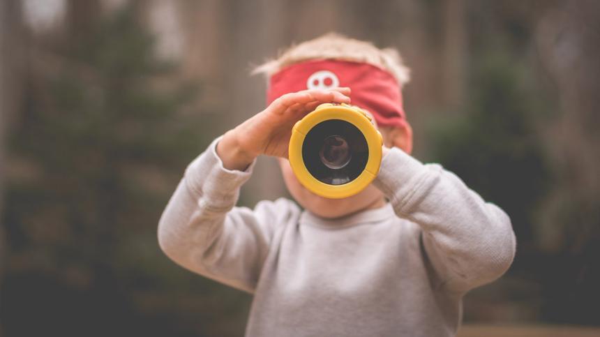 Kind schaut durch ein Fernrohr und trägt ein Stirnband