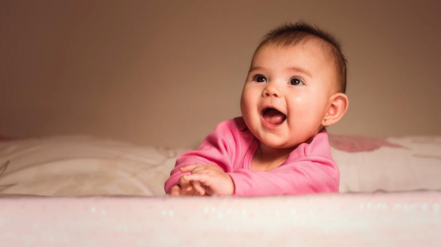 Baby mit pinkem Shirt lacht
