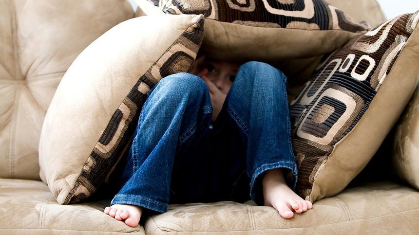 Kind versteckt sich unter Kissen