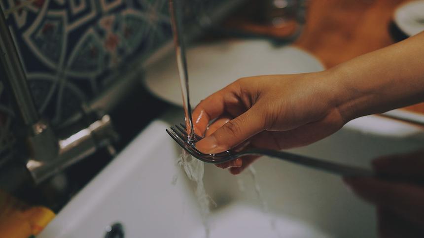 Eine Hand wäscht eine Gabel unter dem laufenden Wasserhahn
