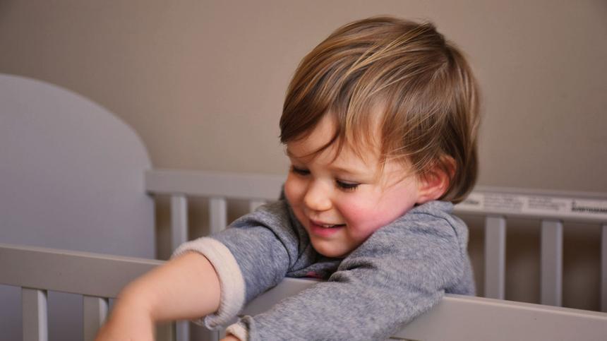 Kleinkind steht in seinem Gitterbett