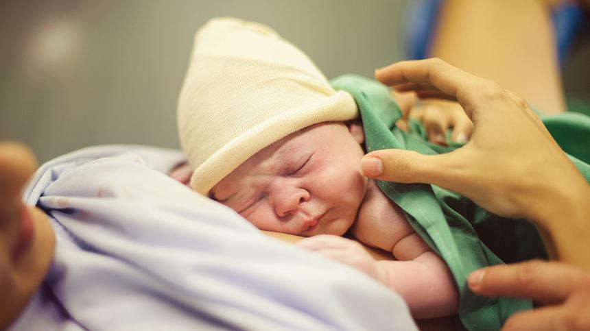 Neugeborenes Baby liegt bei seiner Mama auf der Brust