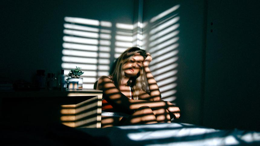 Frau sitzt traurig in einem dunklen Zimmer