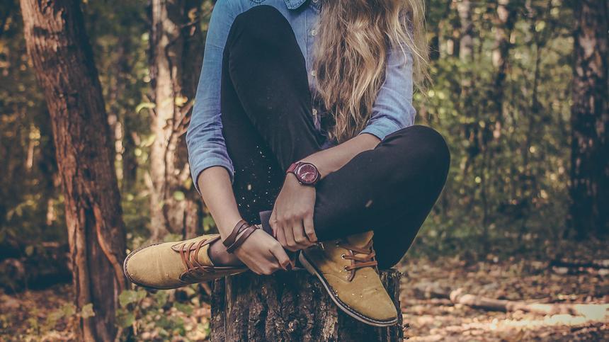 Frau sitzt im Wald