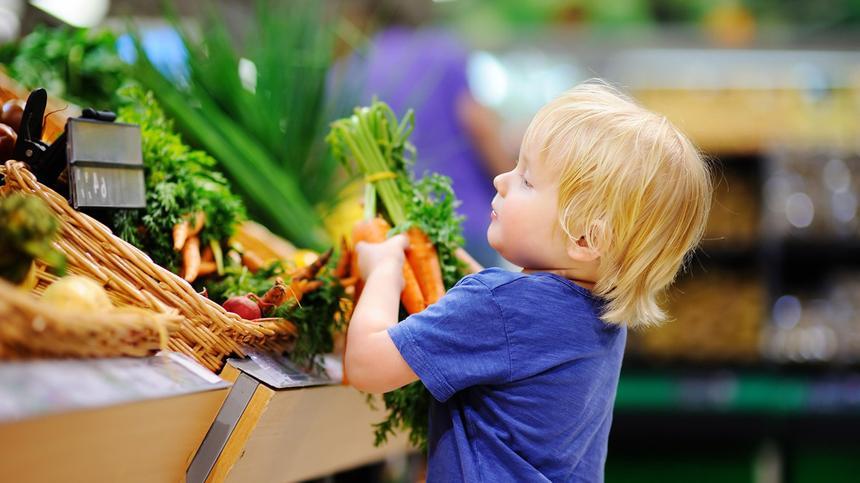 Kind im Supermarkt am Gemüseregal