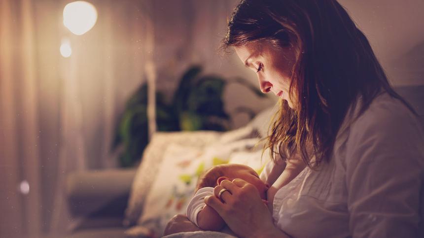 Baby wird nachts von Mutter im Sessel gestillt