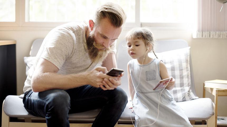 Tochter schaut neugierig auf das Smartphone ihres Vaters