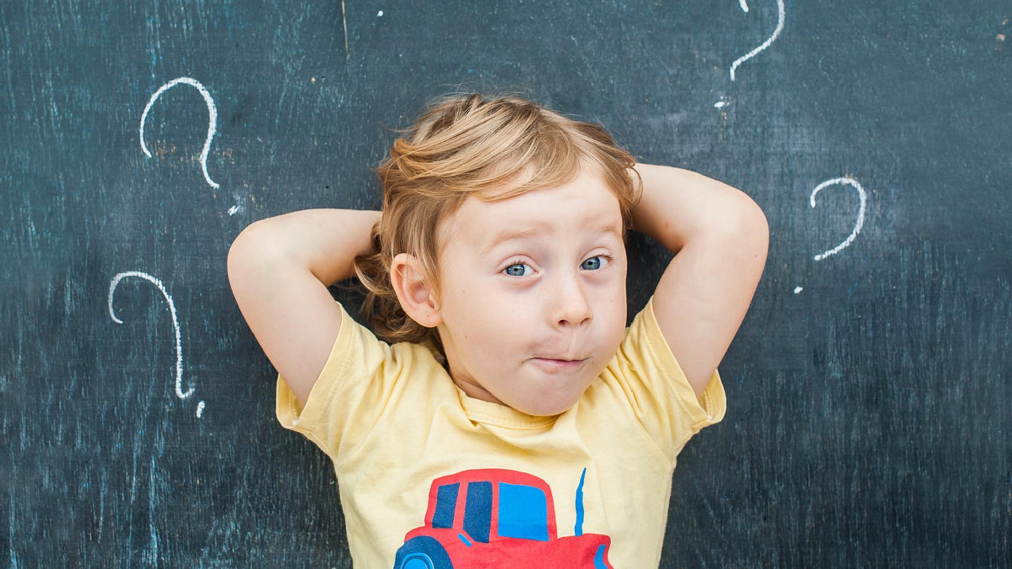 Ein kleiner Junge steht vor einer Tafel mit Fragezeichen.