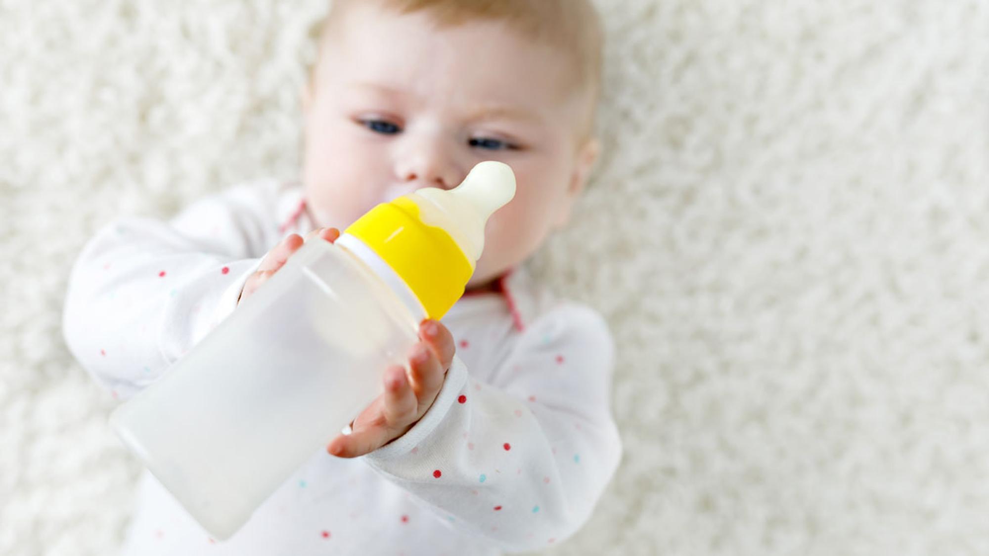 Neugborenes Mädchen hält ein Fläschchen in ihren Händen