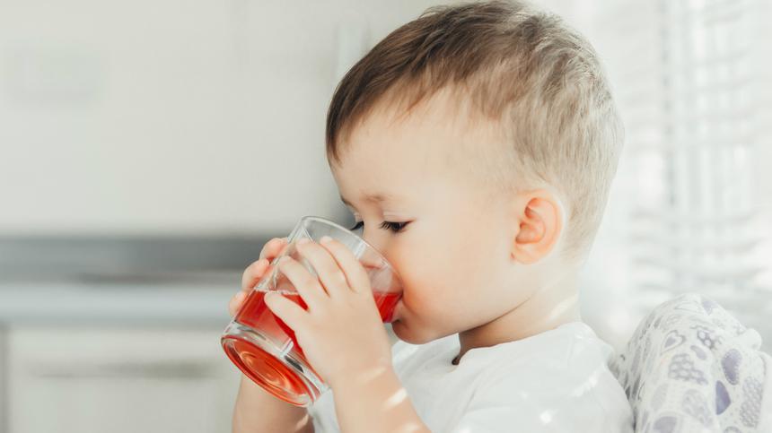 Ein kleiner Junge trinkt ein Glas Saft.