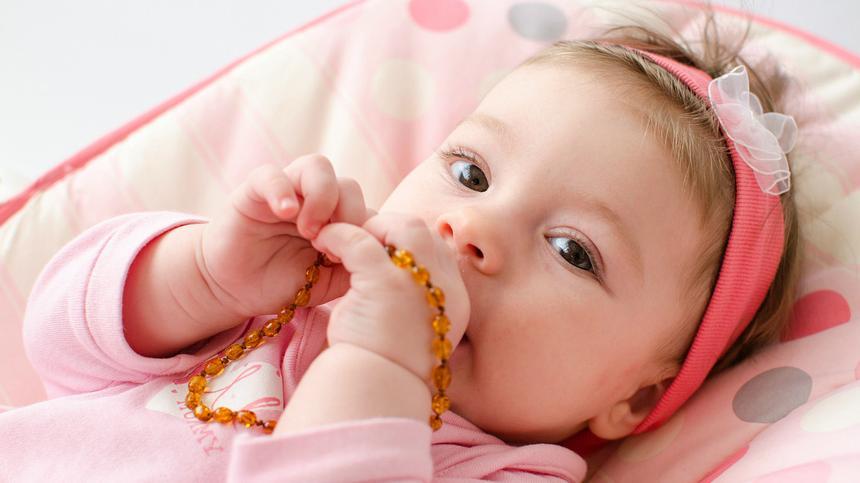 Ein Baby kaut an einer Bernsteinkette