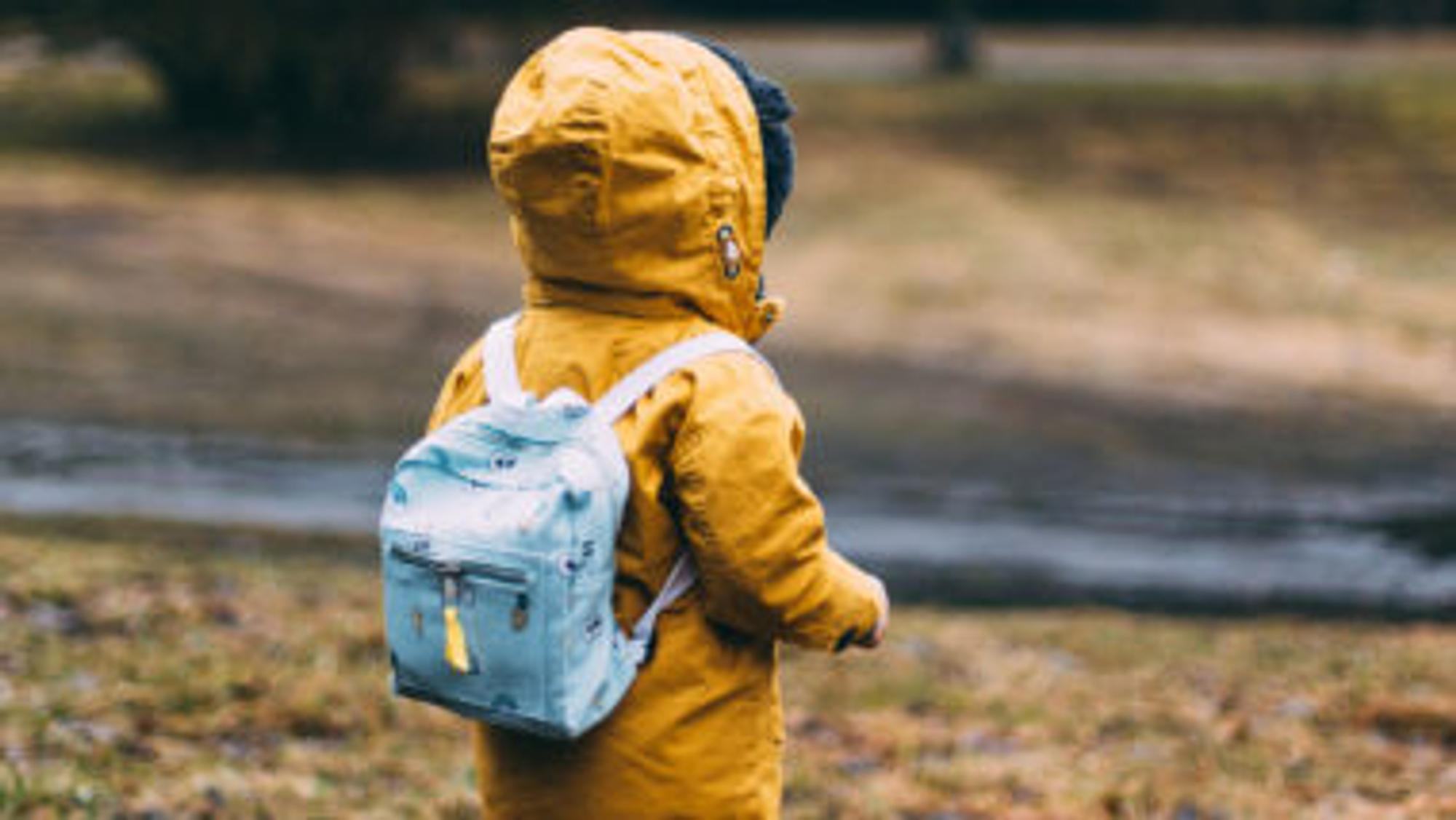 Kind geht mit Rucksack im Wald spazieren