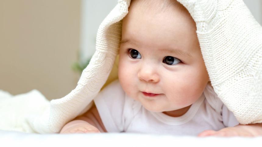 Baby versteckt sich unter Wolldecke