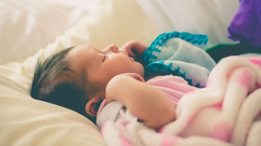 Baby wecken: Baby liegt im Bett