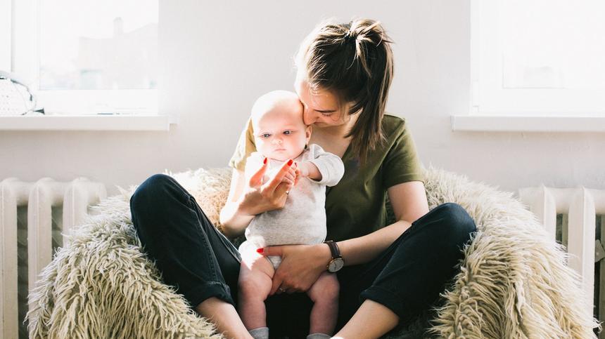 Mutter und Kind kuscheln auf einem Sessel