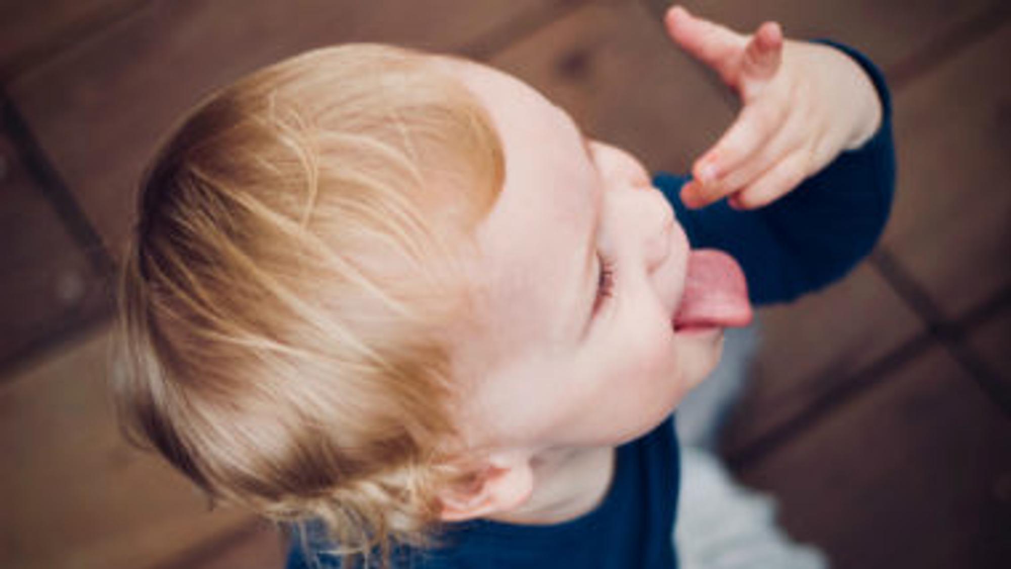 Ein kleiner Junge leckt seine Finger ab