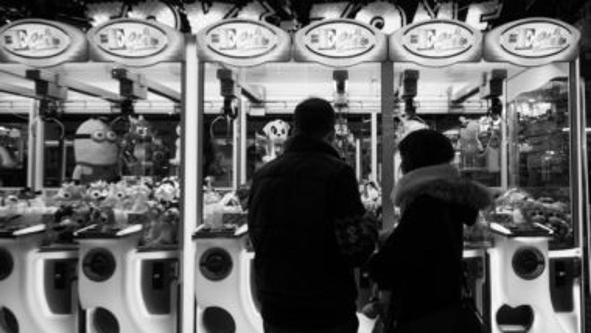 Paar steht vor einer Bude auf einem Jahrmarkt