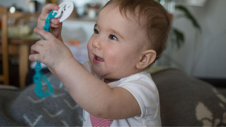 Baby mit Schnullerkette in den Händen
