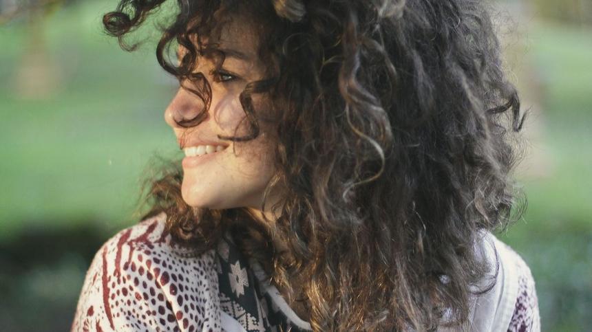Ein Frau mit Lockenkopf lächelt glücklich über Frühschwangerschaft