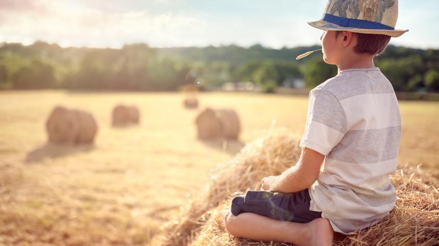 Junge sitzt auf einem Strohballen