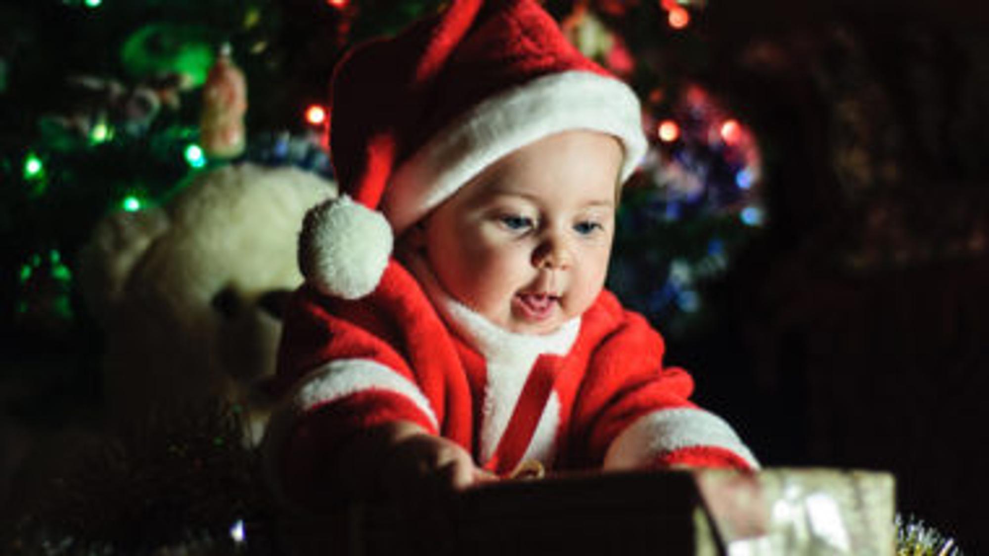 Baby öffnet ein Weihnachtsgeschenk