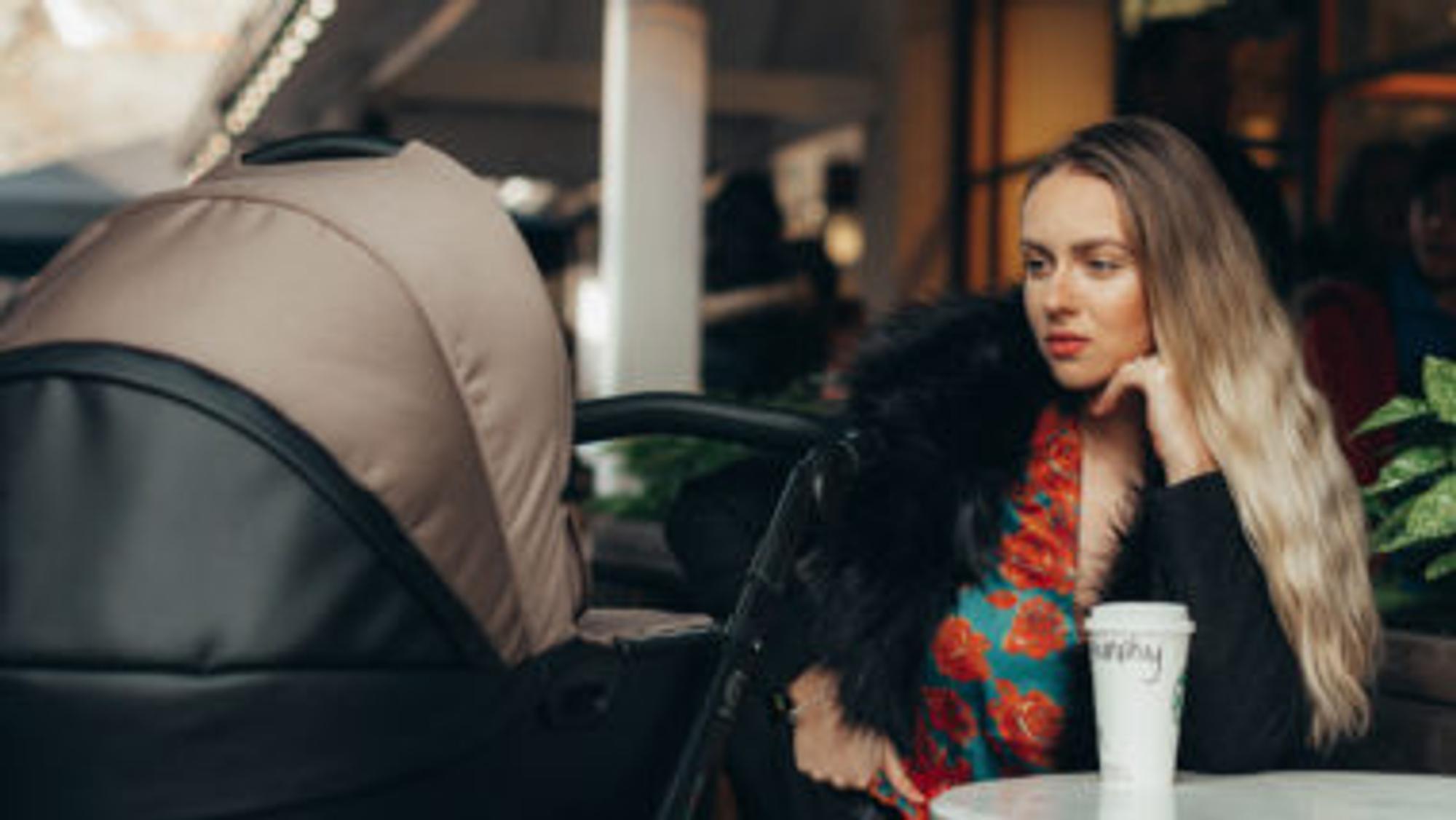 Frau schaut in einem Cafe in einen Kinderwagen