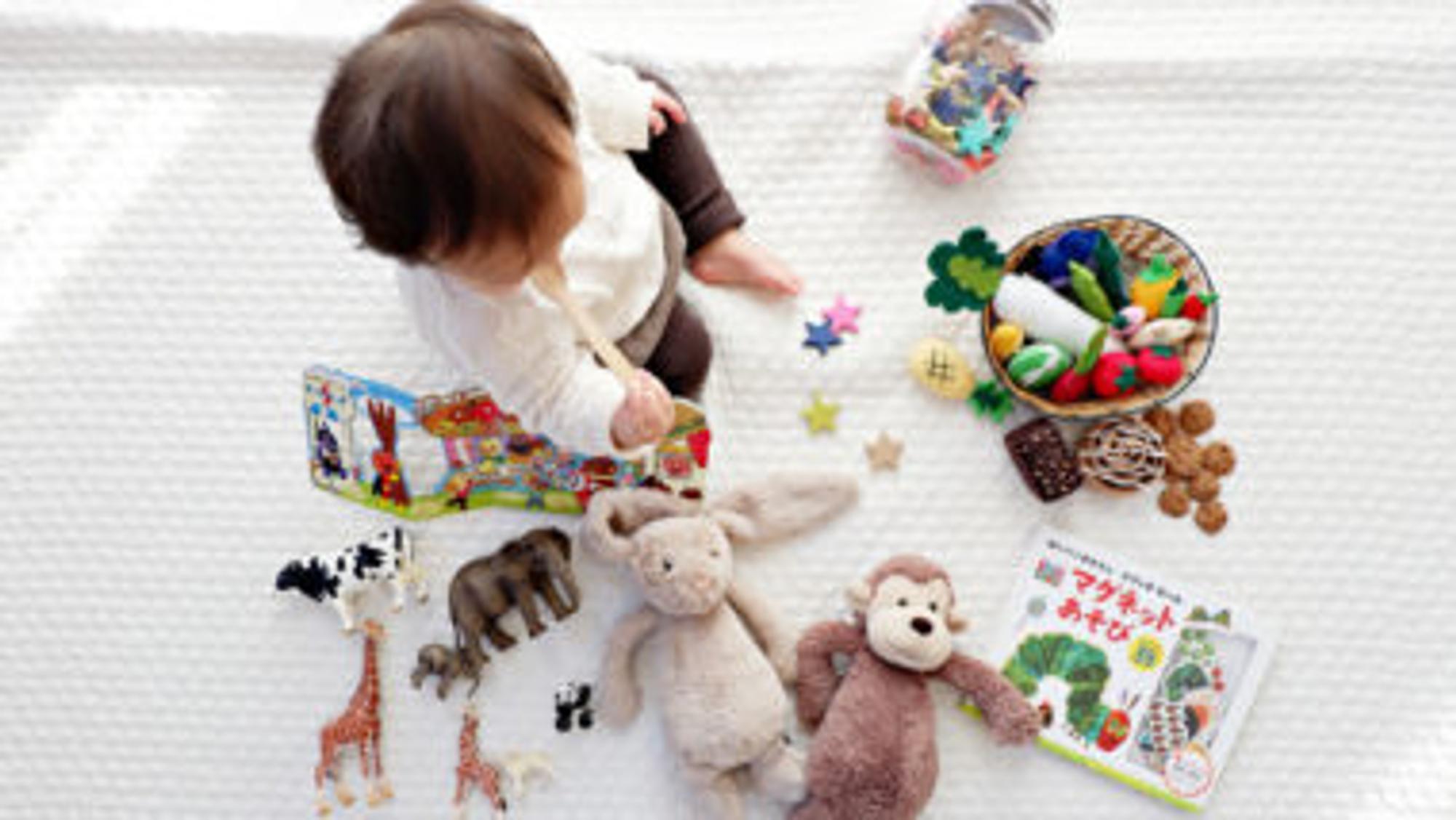 Kind spielt mit verschiedenen Spielsachen