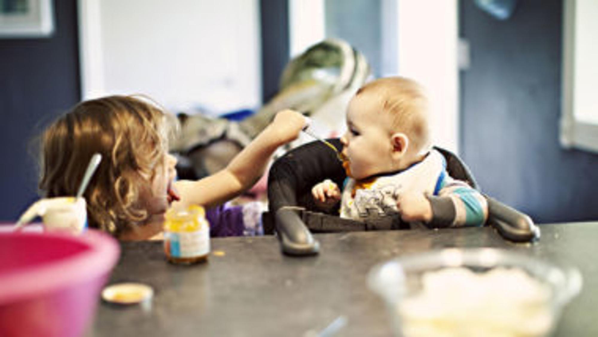 Schwester füttert Baby mit Babybrei: Rezepte hier