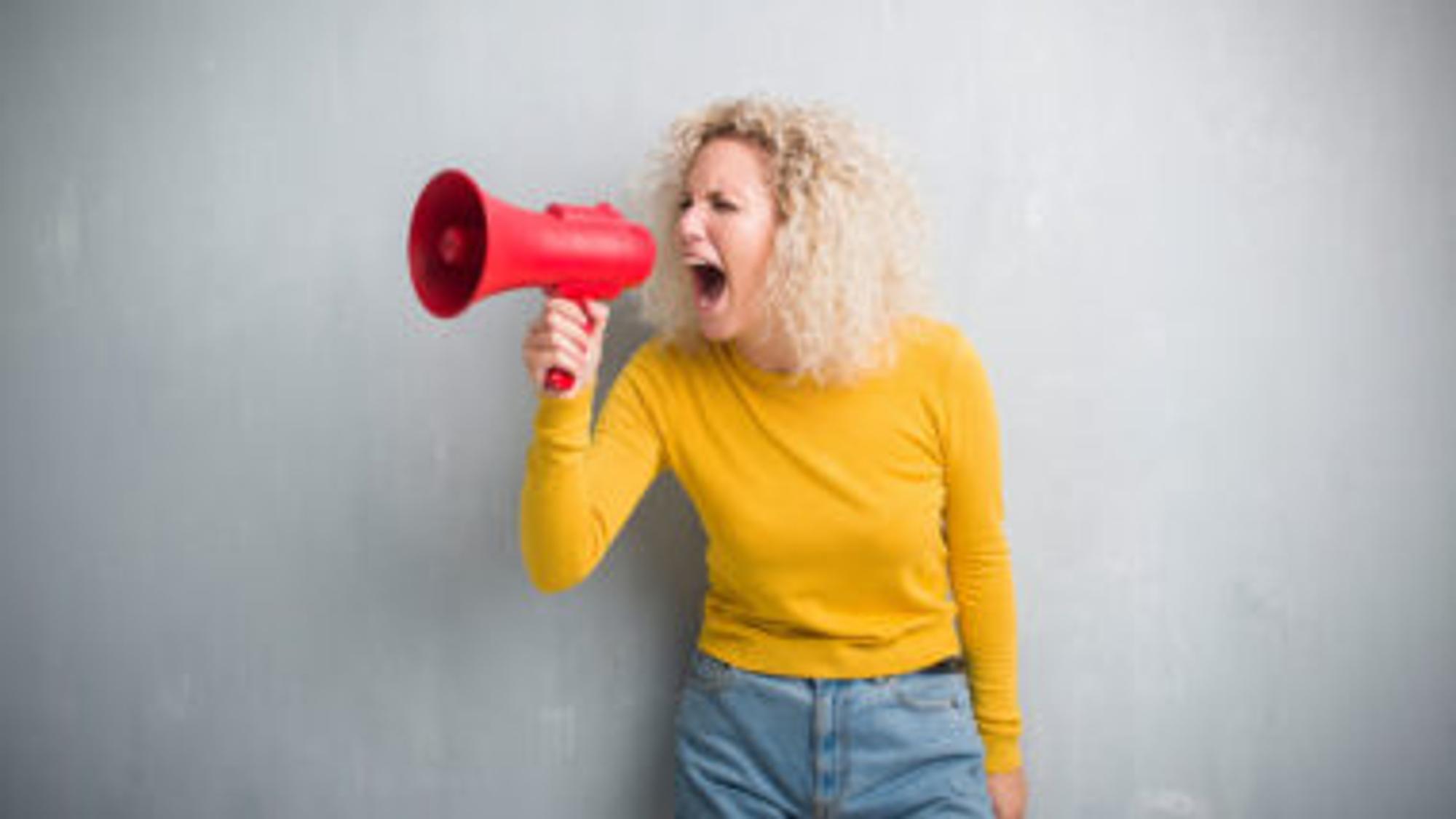 Frau in gelbem Puli schreit in Megafon