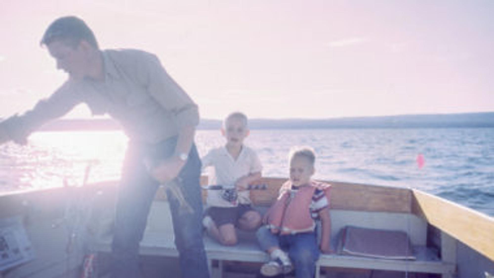 Vater sitzt auf einem Boot mit seinen zwei Söhnen
