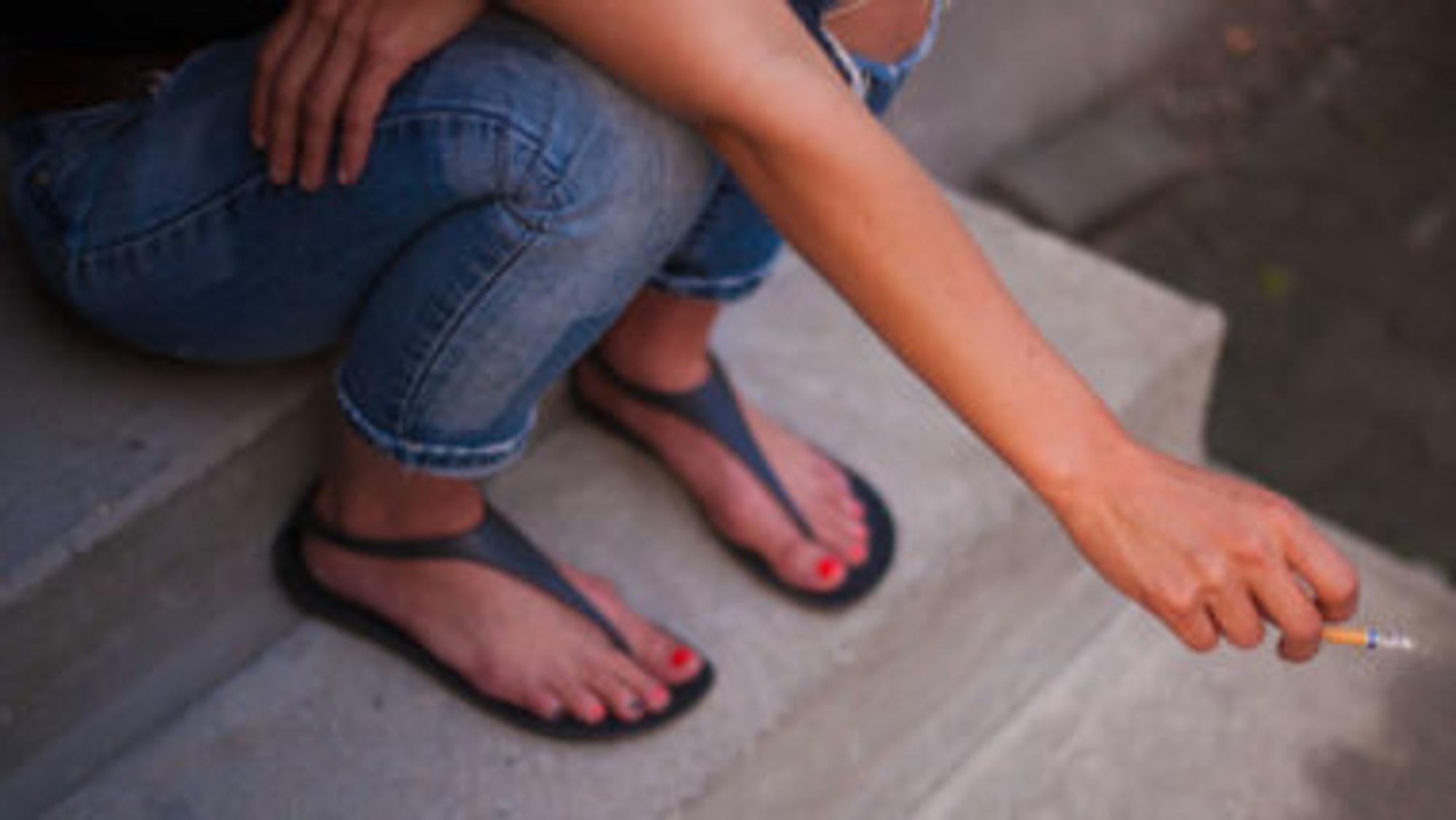 Frau raucht eine Zigarette und sitzt auf einer Treppe