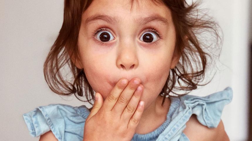 Mädchen reißt überrascht die Augen auf
