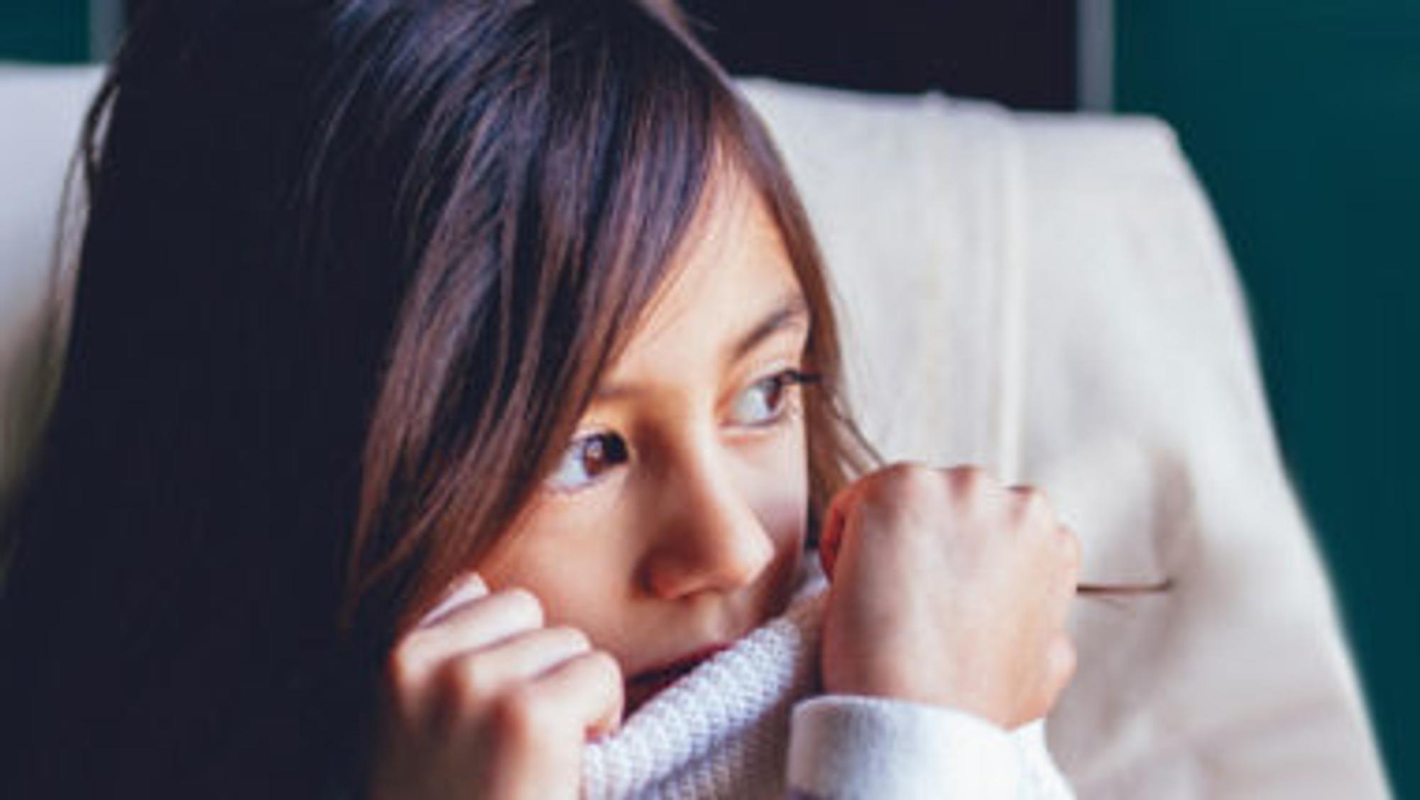 Mädchen traurig , hält sich am Rollkragen fest