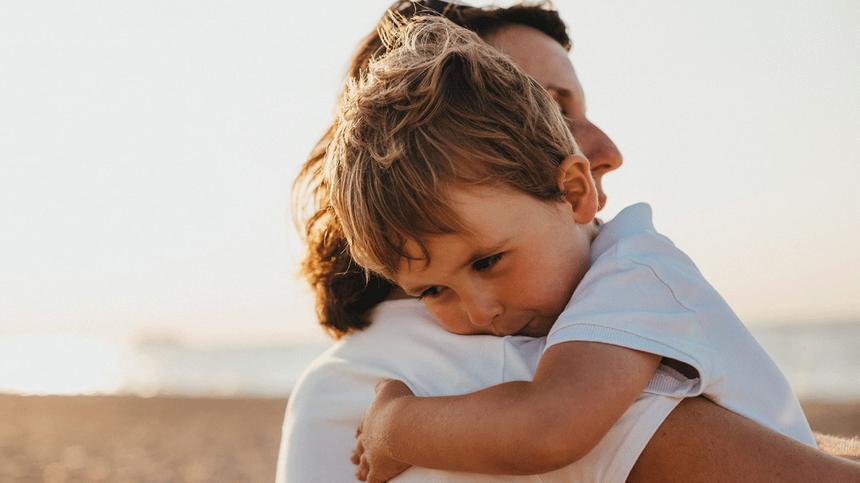 Eine Mutter trägt ihr kleines Kind