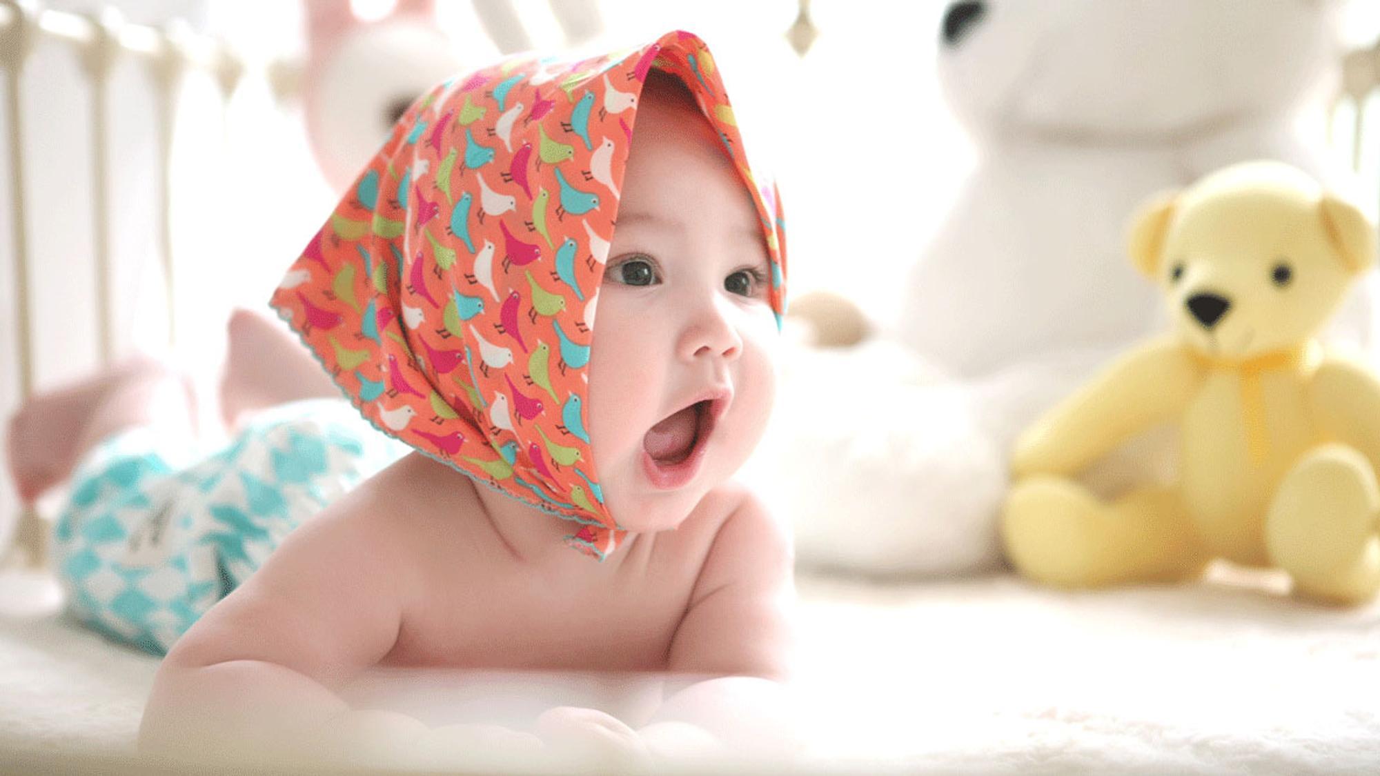 Baby mit Kopftuch und Teddybär