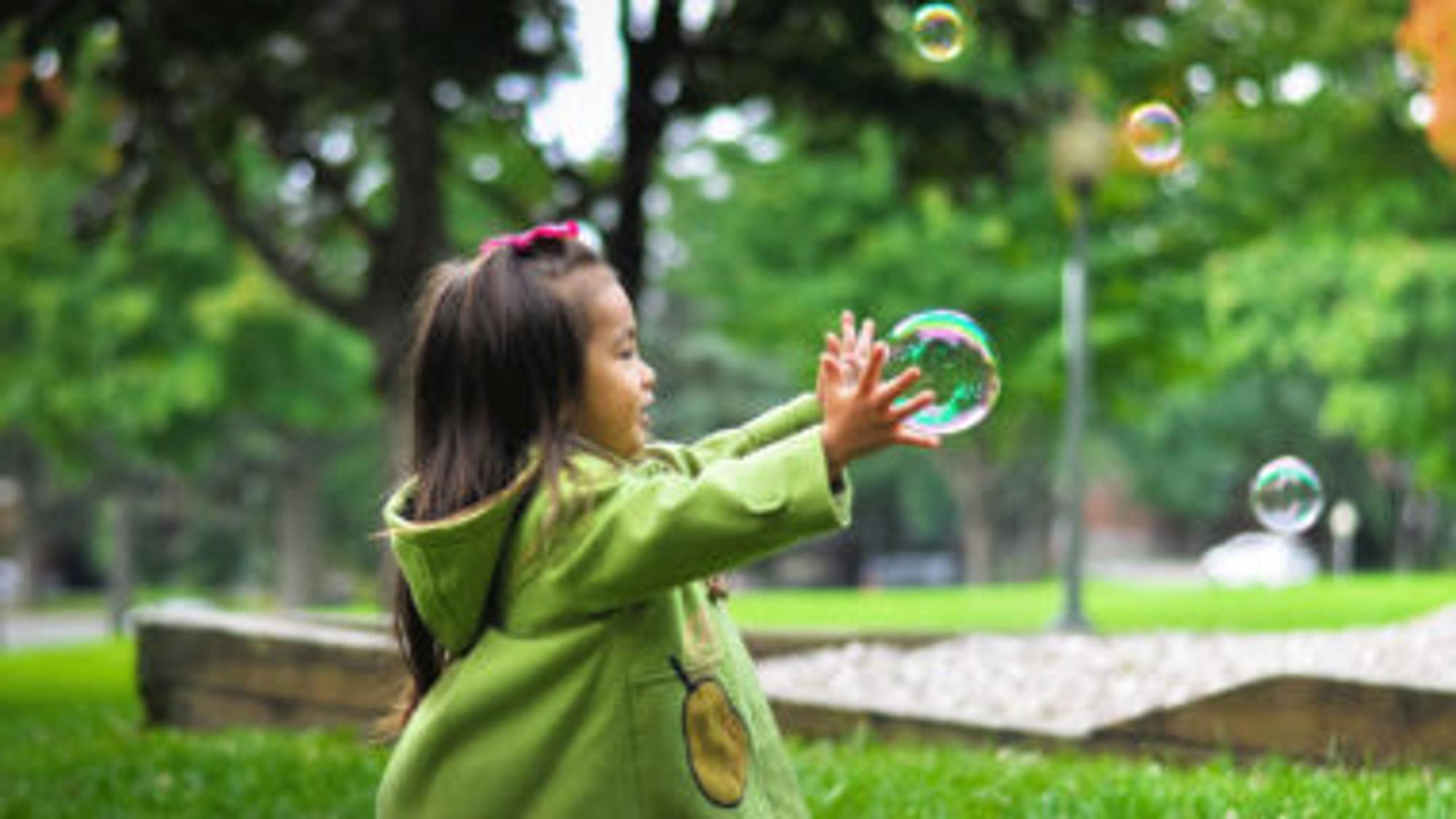 Ein kleines Mädchen, das sorglos im Garten spielt