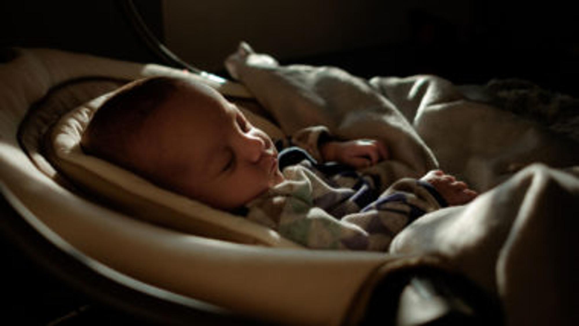 Baby liegt in einer Baby-Wiege